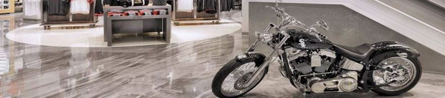 Decorative and Specialty Concrete Material Systems. Metallic epoxy floor coating system in a retail showroom using grey color metallic reflector pigments with 100% solids epoxy and a polyurethane top coat for enhanced abrasion resistance. Beautiful three dimensional metallic floors.